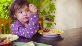 Mała dziewczynka siedzi przy stołem i je smażącą kiełbasę zdjęcie wideo