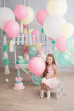 Mała dziewczynka siedzi w pokój dekorujących kolorowych baloons Zdjęcie Stock