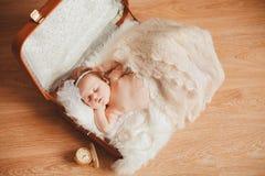 Mała dziewczynka siedzi w walizce. Ciemny tło. Zdjęcia Royalty Free