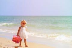 Mała dziewczynka spacer z zabawkami na piasek plaży Obraz Stock