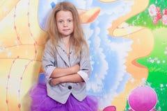 Mała dziewczynka stoi blisko kolorowej ściany fotografia stock