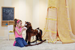 Mała dziewczynka stoi klęczenie przed hobbyhorse Zdjęcia Stock