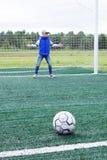 Mała dziewczynka stoi w piłki nożnej bramie jako bramkarz obrazy royalty free