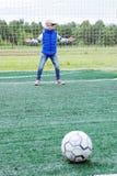 Mała dziewczynka stoi w piłki nożnej bramie jako bramkarz i dostaje przygotowywającą łapać piłkę fotografia stock