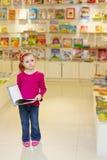 Mała dziewczynka stojaków przyglądającego rozważnego mienia otwarta książka Obrazy Stock