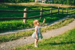 Mała dziewczynka stojaki na kraju raod i punkt na somtheing fotografia stock