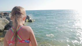 Mała dziewczynka szczęśliwie bawić się z fala przy plażą zbiory