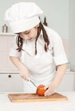 Mała dziewczynka szefa kuchni rezhit pomidory Obraz Royalty Free