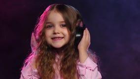 Mała dziewczynka taniec na dymiącym tle w hełmofonach, zwolnione tempo zbiory