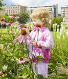 Mała dziewczynka target605_0_ przy kwiaty Obraz Stock