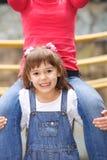 Mała dziewczynka trzyma dalej ramiona dorosły obraz stock