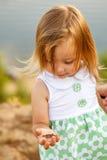 Mała dziewczynka trzyma jej rękę na małej zielonej jaszczurce Obrazy Stock