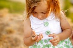 Mała dziewczynka trzyma jej rękę na małej zielonej jaszczurce Obrazy Royalty Free