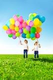 Mała dziewczynka trzyma kolorowych balony. Dziecko bawić się na zieleni Obrazy Stock