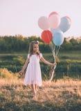Mała dziewczynka trzyma kolorowych balony w łące zdjęcia royalty free