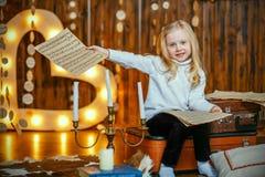 Mała dziewczynka trzyma notatkę w rocznika wnętrzu Obrazy Stock