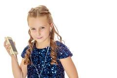 Mała dziewczynka trzyma słuchania i gracza muzyka przez głowy obrazy stock