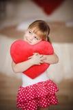 Mała dziewczynka trzyma sercowatą poduszkę czerwona róża matki Zdjęcie Stock