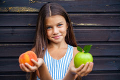 Mała dziewczynka trzyma zielonego jabłka i brzoskwini Obraz Stock