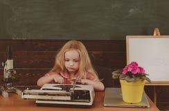 Mała dziewczynka typ na retro maszyna do pisania archaizmu w szkole Przyszłość i archaizm, rocznika filtr zdjęcie stock