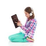 Mała dziewczynka używa cyfrową pastylkę Obrazy Royalty Free
