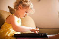 Mała dziewczynka używa pastylka komputer Zdjęcie Stock