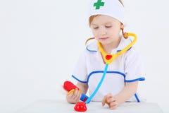 Mała dziewczynka ubierał jako pielęgniarek sztuki z zabawkarskim fonendoskopem zdjęcia royalty free