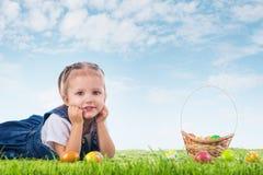 Mała dziewczynka ubierał jako Wielkanocnego królika lying on the beach na trawie z Zdjęcie Stock