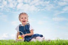 Mała dziewczynka ubierał jako Wielkanocnego królika lying on the beach na trawie z Obrazy Royalty Free