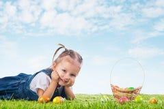 Mała dziewczynka ubierał jako Wielkanocnego królika lying on the beach na trawie z Obraz Royalty Free