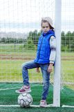Mała dziewczynka ubierał w niebieskich dżinsach i sleeveless kurtka opierał blisko bramy i stawia jej stopę na piłce fotografia royalty free