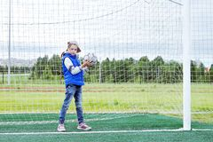 Mała dziewczynka ubierał w niebieskich dżinsach i sleeveless kurtki pozyci w futbolowej bramie z futbolową piłką zdjęcie royalty free