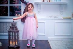 Mała dziewczynka ubierał w piękny moda białego kwiatu smokingowy pozować blisko choinki Fotografia Royalty Free