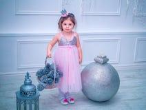 Mała dziewczynka ubierał w piękny moda białego kwiatu smokingowy pozować blisko choinki Fotografia Stock