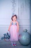 Mała dziewczynka ubierał w piękny moda białego kwiatu smokingowy pozować blisko choinki Obrazy Stock