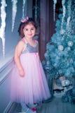 Mała dziewczynka ubierał w piękny moda białego kwiatu smokingowy pozować blisko choinki Zdjęcia Royalty Free