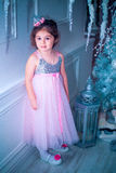 Mała dziewczynka ubierał w piękny moda białego kwiatu smokingowy pozować blisko choinki Zdjęcie Royalty Free