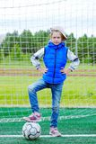 Mała dziewczynka ubierał w, stawia jej stopę na piłce i niebieskich dżinsach i sleeveless kurtki pozyci w futbolowej bramie obrazy stock