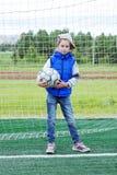 Mała dziewczynka ubierał w, trzyma futbolową piłkę i niebieskich dżinsach i sleeveless kurtki pozyci w futbolowej bramie fotografia royalty free