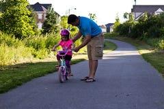 Mała dziewczynka uczenie dlaczego jechać rower z jej tata Zdjęcia Royalty Free