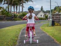 Mała dziewczynka uczenie jechać rower outside fotografia royalty free