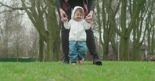 Mała dziewczynka uczy się chodzić z pomocą jej matki zdjęcie wideo
