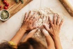 Mała dziewczynka ugniata mąkę z jej matką obraz stock