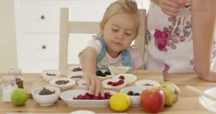 Mała dziewczynka umieszcza jagody na muffins zdjęcie wideo
