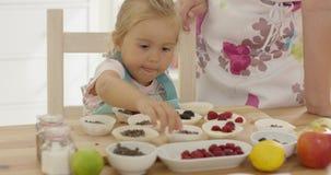 Mała dziewczynka umieszcza jagody na muffins zbiory