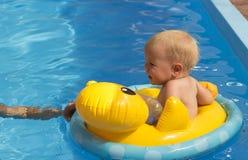 Mała dziewczynka unosi się w basenie w ratowniczej okrąg pomarańcze fotografia stock