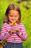 Mała dziewczynka wącha kwiatu obraz stock