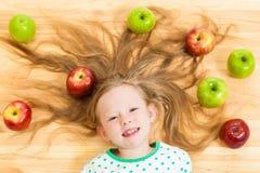 Mała dziewczynka wśród jabłek Obrazy Stock