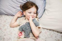 Mała dziewczynka w łóżku bawić się z swój misiem Fotografia Royalty Free