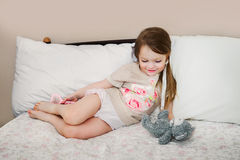 Mała dziewczynka w łóżku bawić się z swój misiem Obrazy Stock